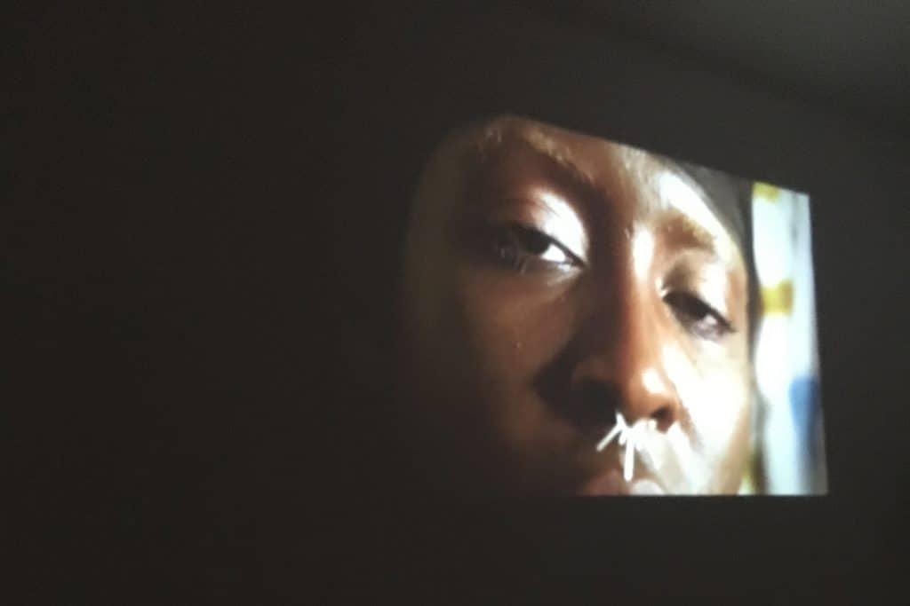 Eine Schwarze Person mit halbgeschlossenen Augen und schwarzem Tuch um den Kopf blickt der Kamera entgegen.