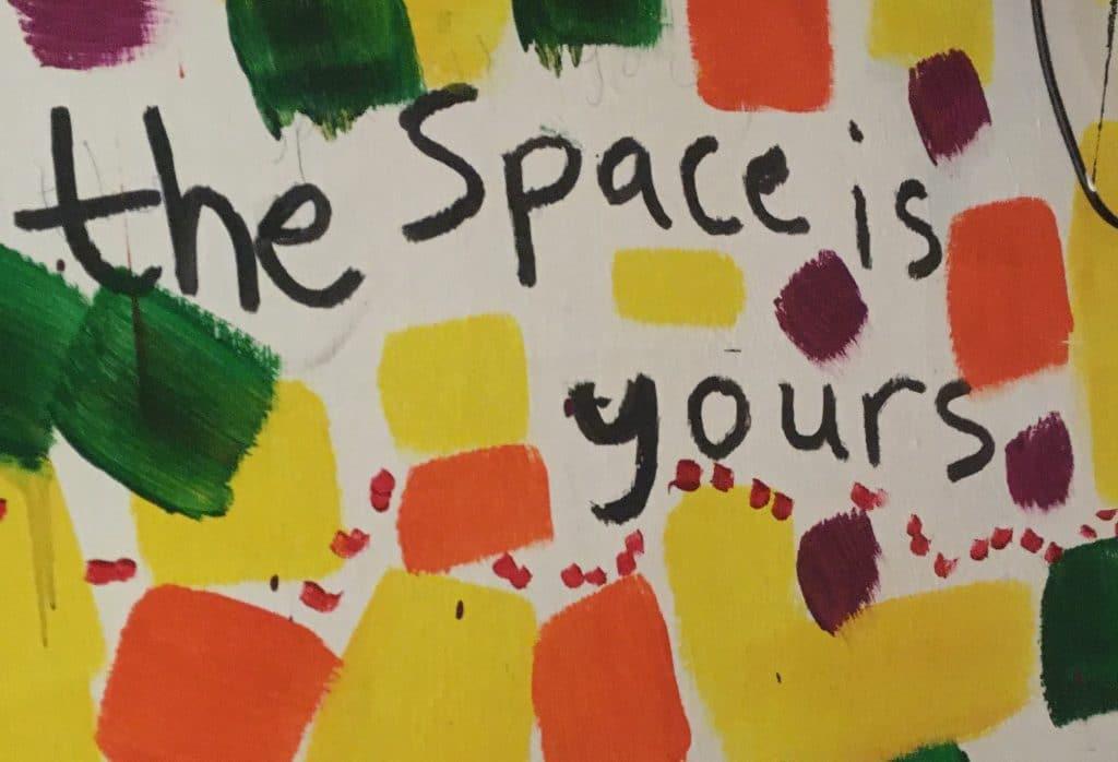 Bunte Farbtupfen in Orange, Gelb, Grün und Violett. 'The Space is yours' in schwarzer Farbe in der Mitte.